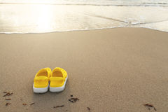 Sandals on the beach. Against a shoreline. Shallow DOF Royalty Free Stock Image