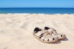 Sandals on the beach near the sea. Royalty Free Stock Image