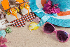 Sandals, blue heat and pink sunglasses on the sand. Summer beach. Concept Stock Photo