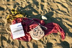 Sandals, book and pareos on the sand Stock Photography