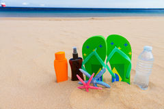 Sandals and bottle of water on sandy beach Royalty Free Stock Photography