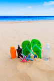 Sandals and bottle of water on sandy beach Royalty Free Stock Photo