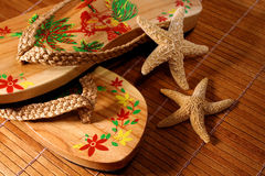 Sandals/ closeup. Pair of beach sandals with little starfish on floor after a days walk on the beach stock image