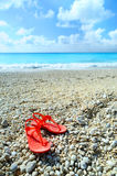 Sandals on an exotic beach. A wide angle shot of a pair of sandals on a beach in Greece Stock Image