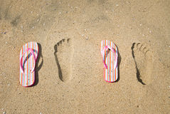 Sandals and footprints in the sand Royalty Free Stock Photos