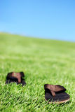 Sandals in grass. Summer Sandals in the grass under a blue sky Royalty Free Stock Photos