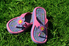 Sandals in the grass. Sandals on a fresh green lawn royalty free stock photos