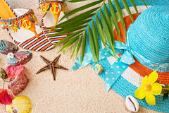 Sandals, hat and sea shelles on the sand. Summer beach concept Stock Photo
