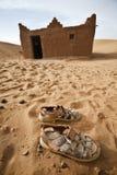 Sandals and house in Sahara desert. Stock Photos