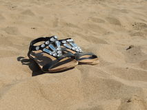 Sandals lying in the sand on the beach Royalty Free Stock Photos