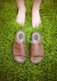 Sandals off. Sandals are placed in front of bare feet on green grass Royalty Free Stock Photos