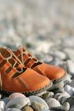 Sandals on a pebbled beach Stock Photos