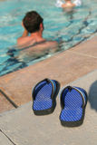 Sandals and pool. Sandals at the edge of a pool royalty free stock photos