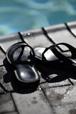 Sandals at poolside. Black sandals beside the pool on the pool deck Stock Photos