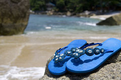 Sandals on a rock at the beach Stock Images