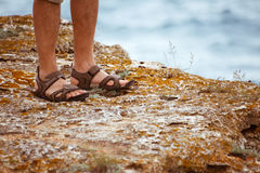 SANDALS ON ROCK NEAR THE SEA Royalty Free Stock Photography