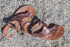 Sandals on a rocky beach. Leather sandals covered by some little stones on a beach  from above Stock Photography
