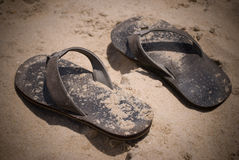 Sandals in the Sand. A pair of sandals or flip flops resting in the sand Stock Image