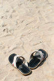 Sandals and sand. Black male sandals standing on the sand Stock Image