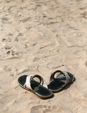 Sandals and sand. Black male sandals standing on the sand Stock Images