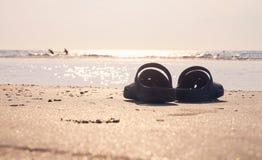 Sandals on the sandy beach. Sandals on the warm sandy beach Royalty Free Stock Photos