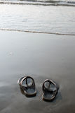 Sandals and sea. Male sandals on the sand at the beach Stock Photography
