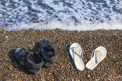 Sandals on sea coast Stock Photos