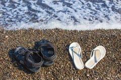 Sandals on sea coast Stock Photos