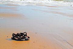 Sandals or shoes on a deserted beach in the summer Royalty Free Stock Photo