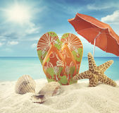 Sandals and starfish with umbrella at the ocean Stock Image
