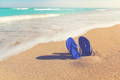 Sandals stuck in the sand of a tropical beach Royalty Free Stock Image
