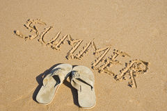 Sandals and summer writing in the sand Royalty Free Stock Photo