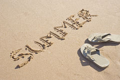 Sandals and summer writing in the sand Royalty Free Stock Photography