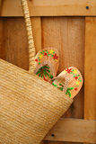 Sandals in sun purse/ closeup. Pair of sandals hanging out of wicker purse royalty free stock images