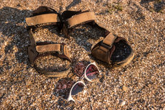 Sandals and sunglasses. Sand with crushed seashells. Bright sun of the tropics. Escape from noise and problems stock images