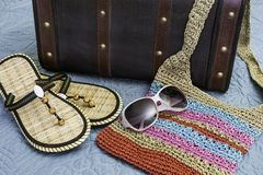 Sandals, sunglasses and tropical weave purse lying on bed ready Royalty Free Stock Images
