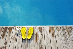 Sandals by a swimming pool Stock Photography