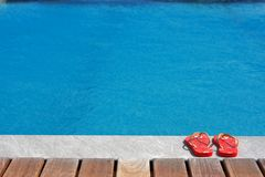 Sandals by the swimming pool Stock Photos