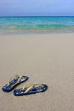 Sandals on a tropical sandy beach. A pair of sandals on a tropical sandy beach Stock Images