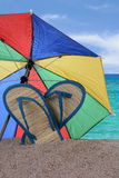 Sandals and Umbrella Stuck in the Sand Stock Photos