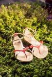 Sandals van de vrouwenzomer liggen op het gras stock fotografie