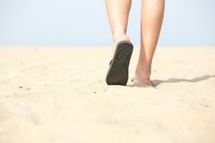 Sandals walking on sand at the beach. Close up feet in sandals walking on sand at the beach Royalty Free Stock Image