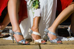 Sandals in Wedding. Feet of the bride among two bridesmaids sitting on chairs and wearing beautiful grey and white high heel buckled sandals while the bride has Royalty Free Stock Photo