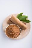 Sandalwood or chandan paste. Ayurvedic Chandan powder or sandalwood paste in silver bowl with sticks and leaves placed over sahan or sahana or circular stone Royalty Free Stock Photo