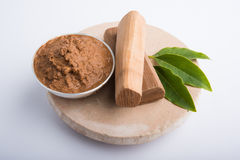 Sandalwood or chandan paste. Ayurvedic Chandan powder or sandalwood paste in silver bowl with sticks and leaves placed over sahan or sahana or circular stone Stock Photo