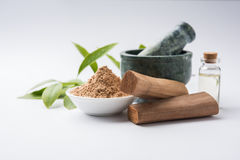 Sandalwood or chandan powder and paste. Chandan or sandalwood powder with traditional mortar, sandalwood sticks, perfume or oil and green leaves. selective focus Stock Photography