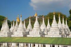 Sandamuni塔的Stupas神圣的小山的背景的 曼德勒,缅甸 免版税库存图片