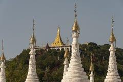 Sandamuni pagoda, in the city of Mandalay. Beautiful golden pagoda surrounded by white stupas. In the city of Mandalay, Myanmar stock photo
