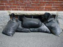 Sandbags. Protecting a basement window from flood damage stock photos