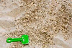 Sandbakgrund med den gröna strandleksaken arkivbild